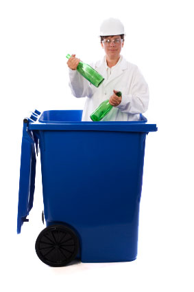 A worker in a white la coat, white hat and safety goggles stands inside a blue recycling bin, holding two empty green beverage containers.